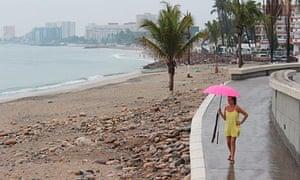 A woman walks along the beach in Puerto Vallarta, Mexico