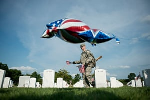 24 hours in pictures: A soldier plants a flag at a grave in at Arlington National Cemetery