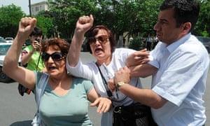 An Azerbaijan plainclothes police officer detains opposition activists in Baku