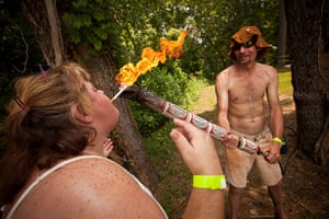 Redneck games: The carrier of the beer can torch lights a woman's cigarette