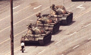 A BEIJING MAN STANDS IN FRONT OF TANK IN TIANEMAN SQUARE.