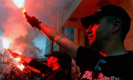 Greek extreme right Golden Dawn party hold red flares outside the town hall of Perama town