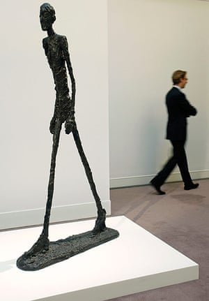 Top ten art auctions: A man walks next to L'homme qui Marche I, by Alberto Giacometti