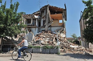 Italy earthquake: A cyclist passes by a damaged building in Rovereto, Modena district, Italy