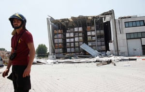 Italy earthquake: A firefighter stands next to a damaged factory in Medolle near Modena