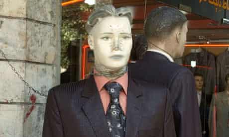 A manikin wearing a suit and tie outside a shop in Tehran