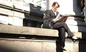 British business woman reading newspaper the city London UK professional director