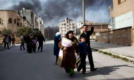 A family escapes from fighting between government troops and Free Syrian Army rebels in Idlib