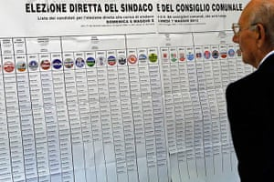Elections: A man studies a list of election candidates at a polling station in Italy
