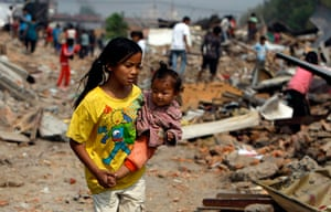 Kathmandu eviction: a Nepalese girl carries an infant
