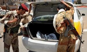 Yemeni soldiers search a car