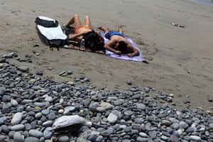 Peru dying pelican: Bathers rest near dead seabirds on the beach at Cerro Azul in Canete, Lima