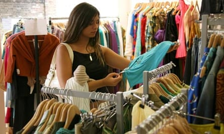 A young woman looking at clothes in a charity shop