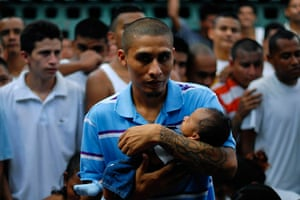 Longer View: An inmate and member of a gang holds his son at the jail in Quetzaltepeque