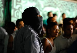 Longer View: A hooded police officer stands near gang members