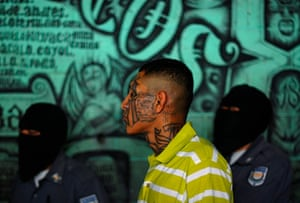 Longer View: A gang member and inmate stands near masked police officers