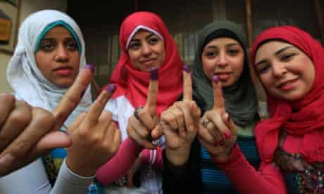 Egyptian women show their ink-stained fingers after voting at a polling station in Cairo
