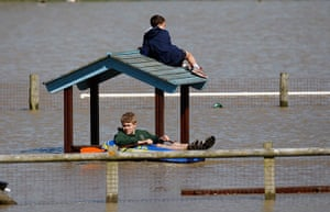 Wales floods: Children play in a flooded play park in the seaside village of Borth