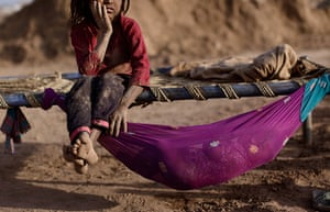 24 hours in pictures: Girl in a brick factory rests on a bed next to her sister, Pakistannagda