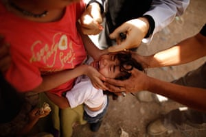 24 hours in pictures: A girl cries as she receives a Polio vaccine shot in Sanaa