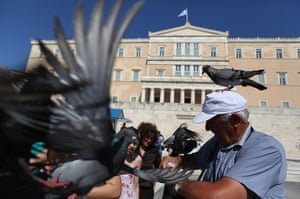 24 hours in pictures: A man is surrounded by pigeons outside the Athens Parliament building