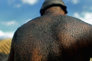 Amazon deforestation : A worker's back is seen covered in charcoal