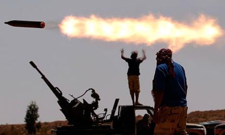 An anti-Gaddafi fighter walk in a village outside Sirte