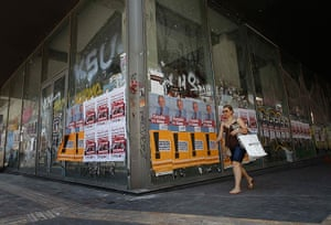 Greece: 13-14 June: A woman walks past a closed shop plastered with election campaign posters