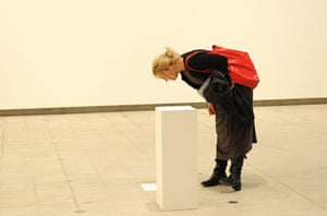 Invisible Art: A woman bends over an exhibit which is a white pillar