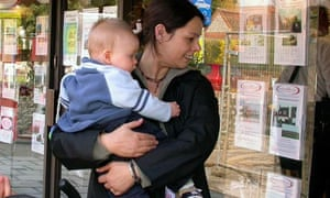 Woman and child looking in estate agent window