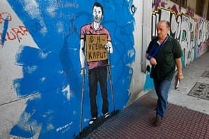 Greece: health system: A man walks past a graffiti