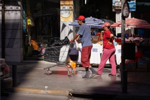 Andy Hall Athens: A couple walk across town with their possessions in a shopping trolley
