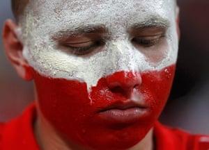 Group A3: Tears create streaks in the face paint of a Polish fan