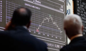 Traders look at computer boards at the stock exchange in Madrid