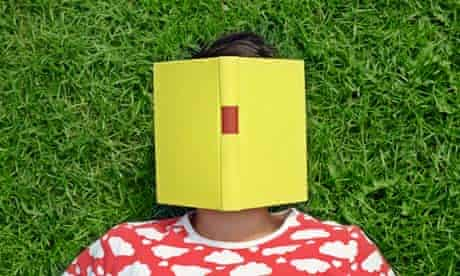 woman lying on the grass with a book on her face