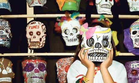 Mexican girl wearing a skull mask for the Day of the Dead