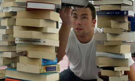 bookseller with towers of second-hand books