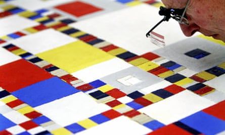 A researcher inspects a painting by Piet Mondrian