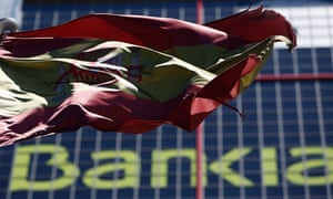 A Spanish flag flutters in front of the headquarters of Bankia