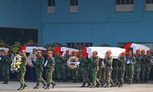 Members of the Indonesian air force carry the coffins of the victims of the plane crash in Jakarta
