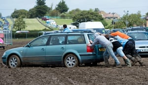 ISle of Woght: Festival-goers attempt to push a car out of the mud