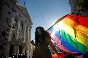 Gay pride week: Lisbon, Portugal: A reveler walks past a church during the parade