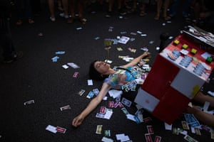 24 hours in pictures: A protester lays on the ground covered by fake notes, Spain