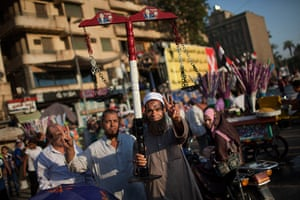 24 hours in pictures: A man flashes the victory sign as he carries a scale, Cairo