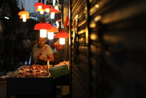 24 hours in pictures: A woman inspects fresh seafood at a wet market in Hong Kong