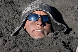 24 hours in pictures: A local resident buries himself into an ash deposit during a protest