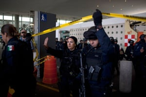 24 hours in pictures: Federal police officers lift a strip of crime scene barrier tape, Mexico