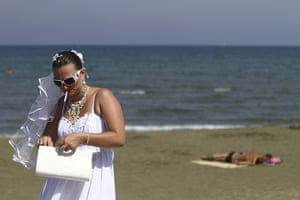 24 hours in pictures: A bride smokes a cigarette on the beach after a mass civil ceremony