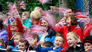 Queen: Members of the public wave their Union Jack flags as they wait the Queen