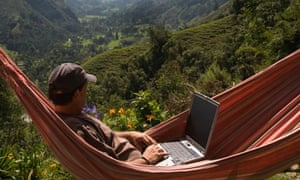 A man relaxes in a hammock whilst using his laptop